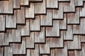 Wooden roof shingles. An ancient house roof, consisting of wooden roof shingles, which are arranged in a pattern.