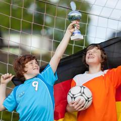 zwei junge fußballer jubeln mit pokal