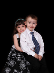 adorable portrait of brother and sister sitting. isolated