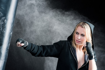 Blond boxing woman in black punching bag