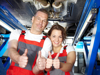 Two motor mechanics at work and show thumbs up