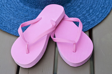 Pink Flip Flop and Blue Straw Hat on a Deck