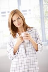 Attractive girl in pyjama drinking tea smiling