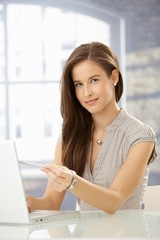 Young woman pointing at laptop screen