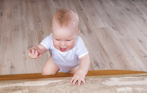 lovely smiling baby crawling on the stairs
