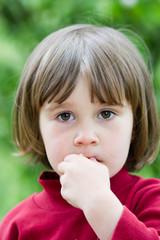 Little girl eats a sandwich