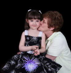 proud grandmother kissing young granddaughter. isolated