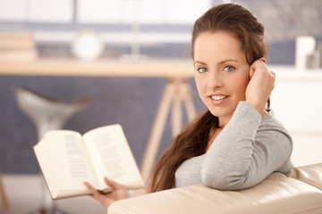 Attractive girl reading book on sofa at home