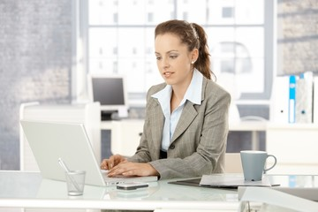 Attractive woman working on laptop in office