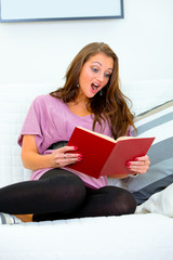 Shocked  woman sitting on sofa at home and reading  book.