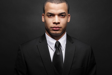 Young African-American businessman in black suit.