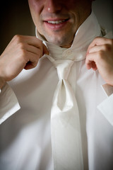 man fixing tie formal wear