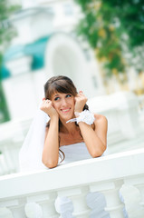 pensive smiles bride in a white dress has leant the elbows on ha