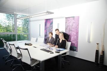 3 Geschäftsleute im Büro bei Besprechung