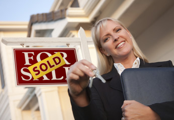 Real Estate Agent with Keys in Front of Sold Sign and House