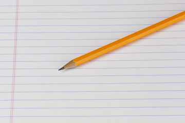 A yellow pencil on a piece of notebook paper