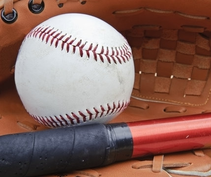 Close up of baseball in catcher's mitt with bat and shallow dep