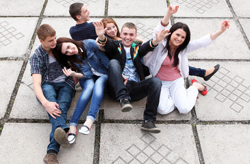 Group of male and female students sitting on street