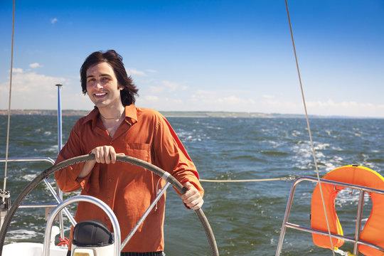 Young  skipper driving sailboat