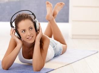 Attractive girl listening music laying on floor