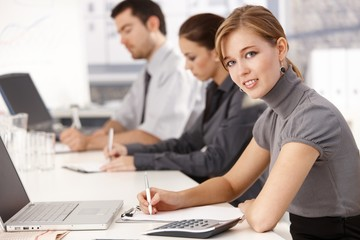 Young businesspeople sitting at meeting table