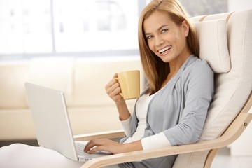 Happy young woman with computer and coffee mug