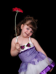 little girl in ballet outfit holding flower. isolated