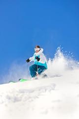 Female Powder Skiing against Colorado Blue Sky