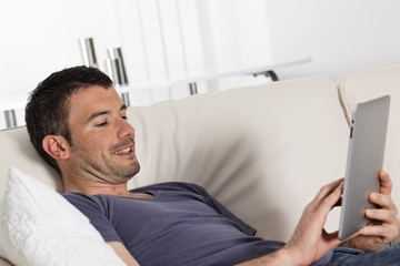 man using tablet pc on sofa at home