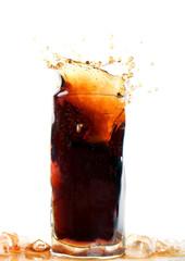 Glass of cola splashing, isolated on white background