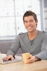 Happy young man sitting at table