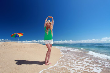 久高島のビーチで背伸びをする笑顔の女性