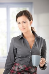 Pretty female smiling with tea mug in hand