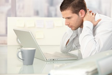 Young man looking tired in office