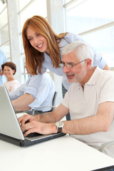 Senior man with trainer in front of laptop computer