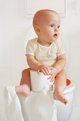 Cute baby sitting on a toilette