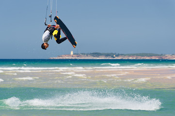 Kiteboarder surfing waves and jump