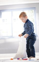 Cute little boy unpacking bag with toys