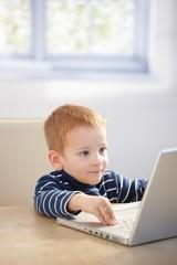 Sweet gingerish kid playing video game on laptop