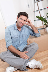 Handsome smiling man sitting on the floor