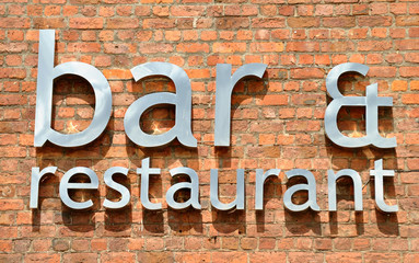 metal bar and restaurant sign on a brick wall