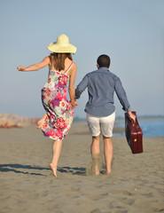 couple on beach with travel bag