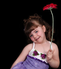 sweet little girl in ballet outfit holding flower. isolated
