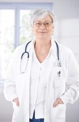 Senior female doctor smiling at hospital corridor