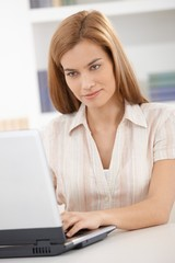 Portrait of young woman using laptop smiling