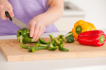 Woman cutting vegetables in modern kitchen interior