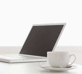 Modern laptop and cup of tea on a table