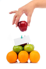 Colorful pyramid of fruits with a hand hold an apple gently