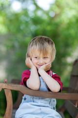 kleiner junge sitzt auf gartenbank