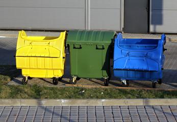 three plastic big trash recycling bins on the street